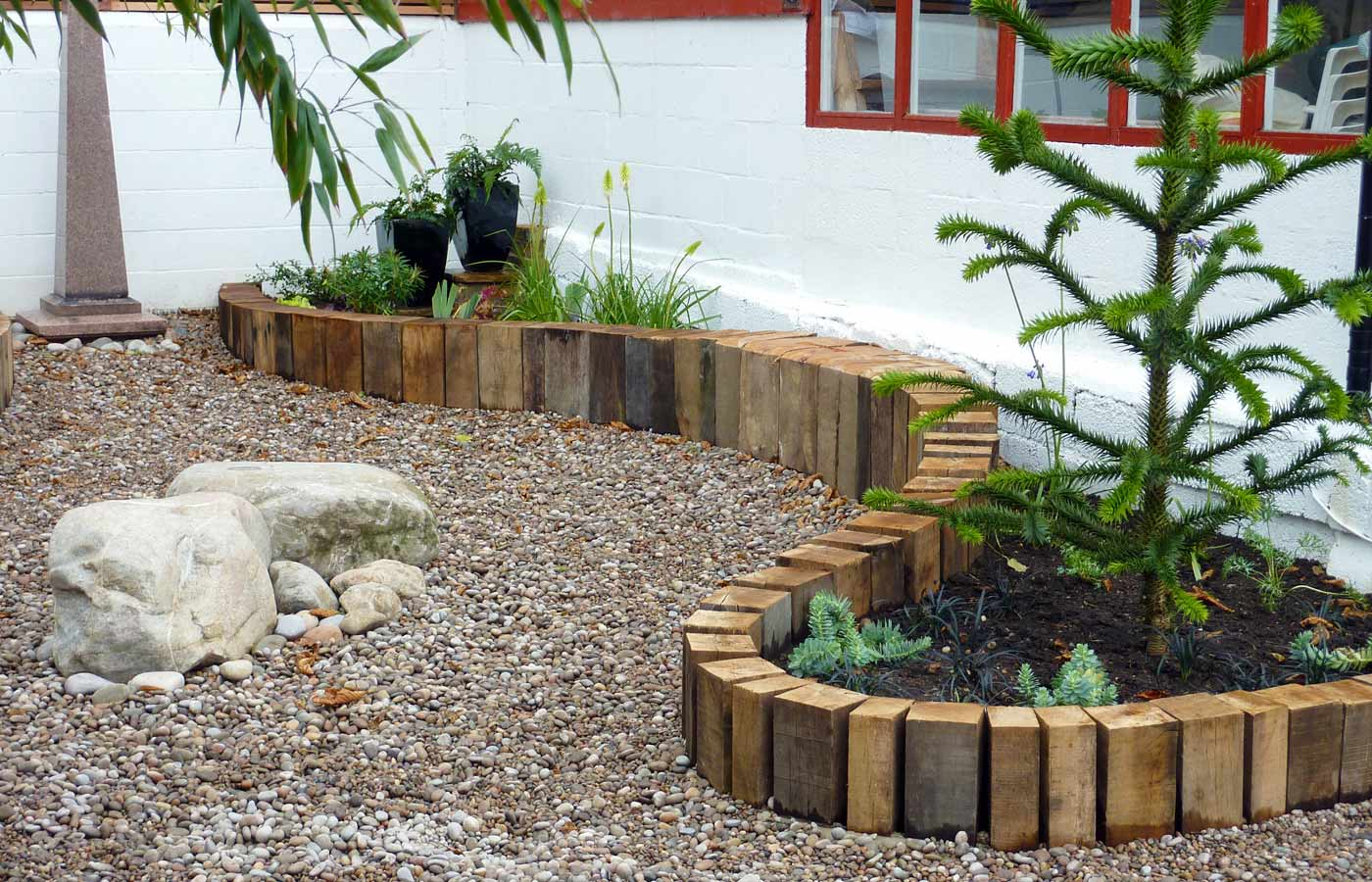 Reclaimed oak beams contain the planting areas and provide seating