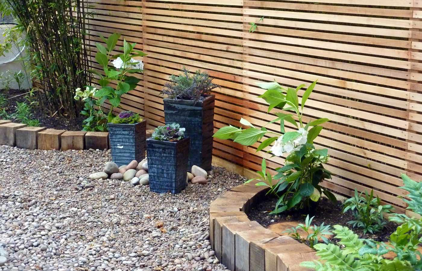 Rugged planters create an accent between planting areas