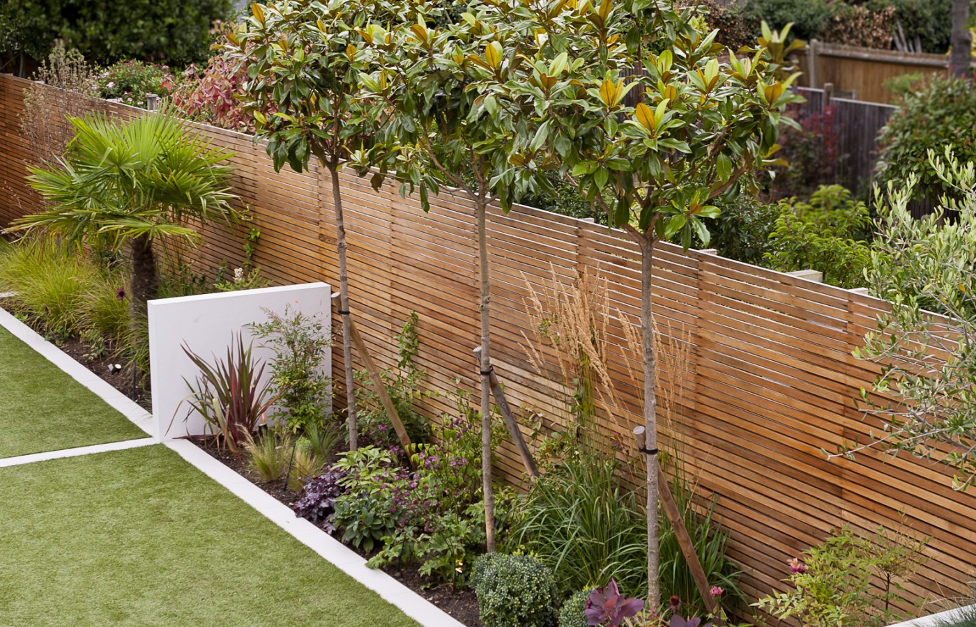 long thin garden design from the patio showing wooden seating and family planting in contained flowerbeds edging the lawn