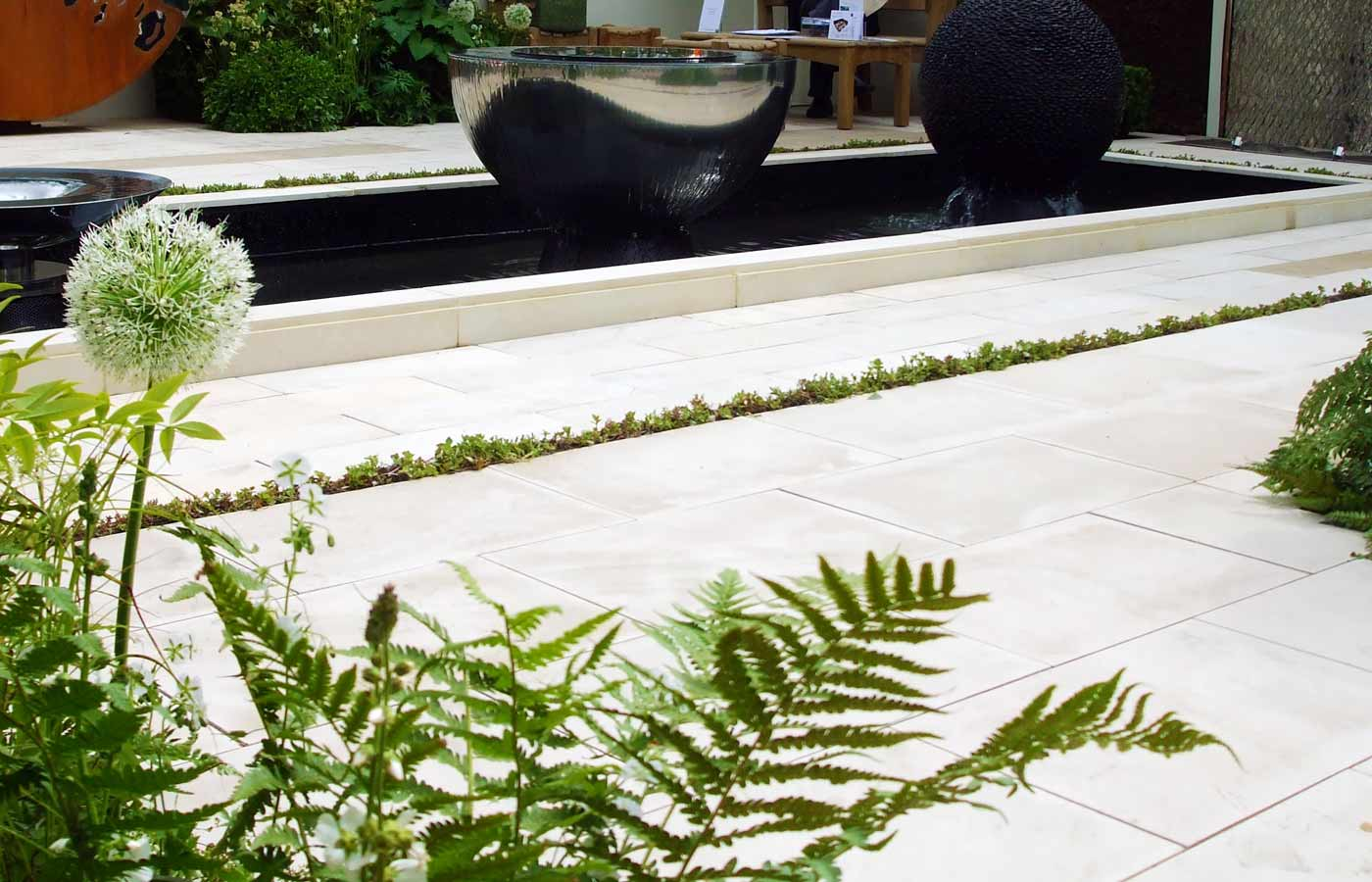 White and green planting smooth sandstone reflect in chalice water feature