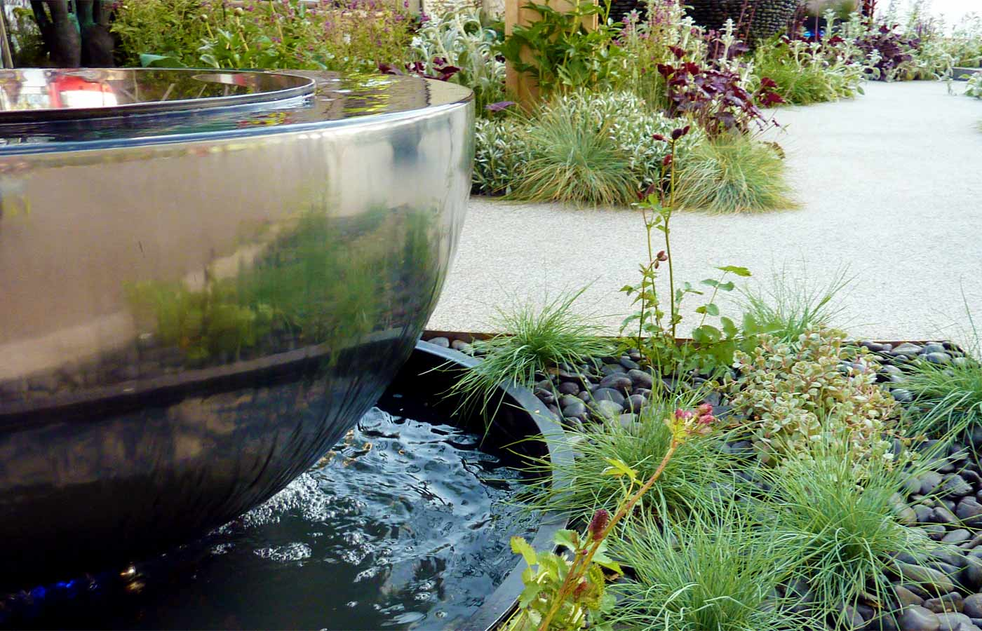 Pebbles and grasses provide a foil for a glittering water feature