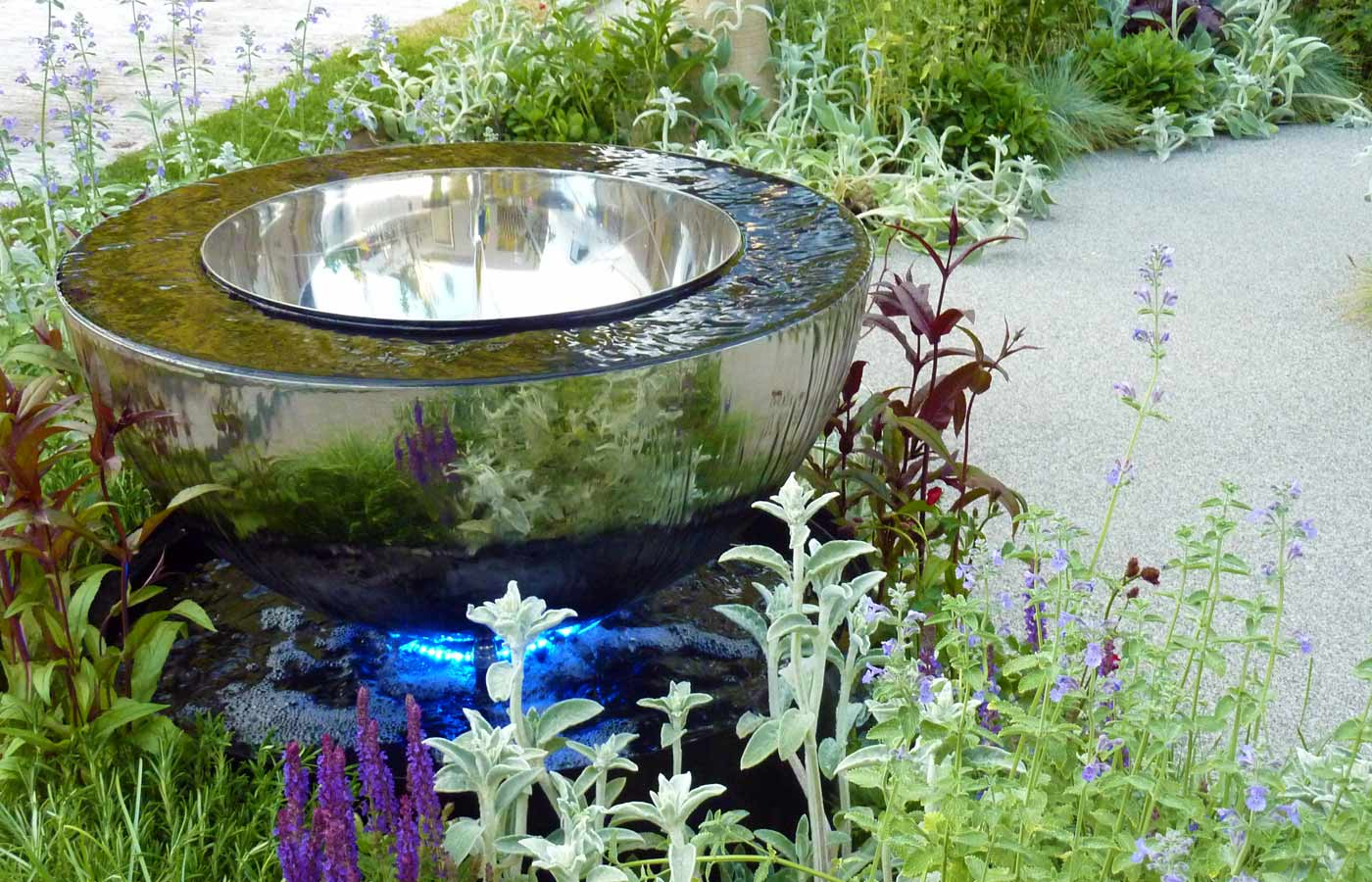 Water feature emerging from massed silver and purple planting